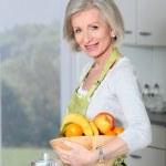 Smiling senior woman in kitchen — Stock Photo #5697410