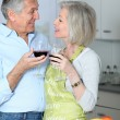 Senior couple drinking wine in kitchen — Stock Photo
