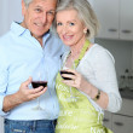 Senior couple drinking wine in kitchen — Stock Photo