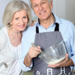 Happy senior couple baking together — Stock Photo
