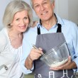 Stock Photo: Happy senior couple baking together