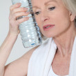 Portrait of senior woman with bottle of water after exercising — Stock Photo #5697681