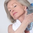 Portrait of senior woman with bottle of water after exercising — Stock Photo #5697682