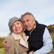 Happy senior couple embracing each other in countryside — Stock Photo #5697728