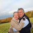 Happy senior couple embracing each other in countryside — Stock Photo