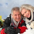 Senior couple having fun at ski resort - Stock Photo