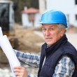 Architect with drawing on construction site - Stock Photo