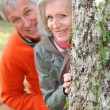 Closeup of senior couple hiding behind a tree — Stock Photo