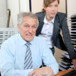 Senior businessman with young woman in the office — Stock Photo