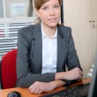 Young woman in office in front of computer — Stock Photo