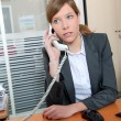 Young woman in the office talking on the phone — Stock Photo