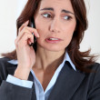 Businesswoman on the phone with preoccupied look - Stock Photo