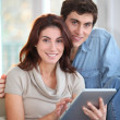 Stock Photo: Young couple using electronic tablet at home