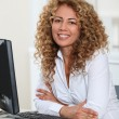 Businesswoman sitting at her desk in office — Stock Photo #5698534