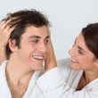 Young woman putting her hands in her boyfriend's hair — Foto Stock