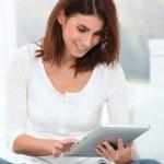 ung kvinna sitter på soffan med elektroniska tablett — Stockfoto
