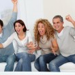 Foto de Stock  : Group of friends sitting in sofwatching tv