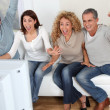 Group of friends sitting in sofa watching tv — Stockfoto