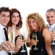 Group of friends cheering with glasses of champagne - Stock Photo