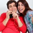Couple having fun listening to music player — Stock Photo