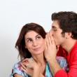 Young man whispering in his girlfriend's ear — Stock Photo #5699270