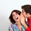 Young man whispering in his girlfriend's ear — Stock Photo #5699272