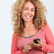 Portrait of blond woman listening to music player — Stockfoto