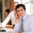 Businessman in the office talking on the phone — Stockfoto
