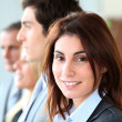 Smiling businesswoman standing amongst a group — Stock Photo