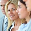 Smiling businesswoman standing amongst a group — Stock Photo #5699580