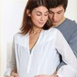 Parents with hands on pregnant woman's belly — Stock Photo #5699771