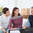 Young couple signing contract for home moving - Stock Photo