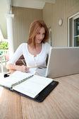 Mujer que trabaja en su casa en ordenador portátil — Foto de Stock