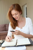 Self-employed woman at home talking on the phone — Stock Photo