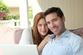 Couple sitting in couch with laptop computer — Stock Photo
