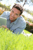 Man with electronic tablet in public park — Stock Photo