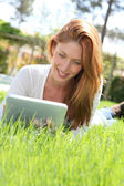 Beautiful woman websurfing with electronic tablet — Stock Photo