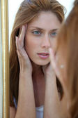 Beautiful woman looking in a mirror — Stock Photo
