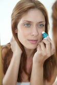 Beautiful woman putting concealer on her eyes — Stock Photo