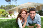 Happy couple laying down in their home garden — Stock Photo
