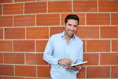 Attractive man using electronic tablet leant on brickwall — Stock Photo