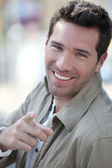 Portrait of handsome man pointing at camera — Stock Photo