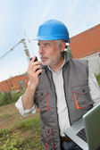 Construction manager on building site with laptop computer — Stock Photo