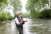 Man fishing trout in river — Stock Photo