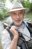 Portrait of smiling fisherman on riverside — Stock Photo