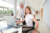 Woman in wheelchair with trainer in office — Stock Photo