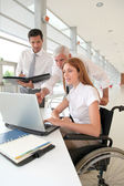 Handicapped woman attending a meeting in office — Stock Photo