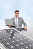 Businessman standing by solar panels — Stock Photo