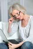Senior woman sitting in sofa with laptop computer — Stock Photo