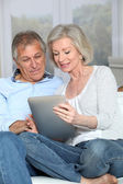Senior couple surfing on internet with electronic tablet — Stock Photo